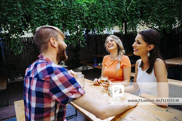 Happy friends drinking spritzer at outdoor pub