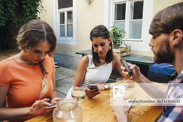 Friends using cell phones and drinking spritzer at outdoor pub
