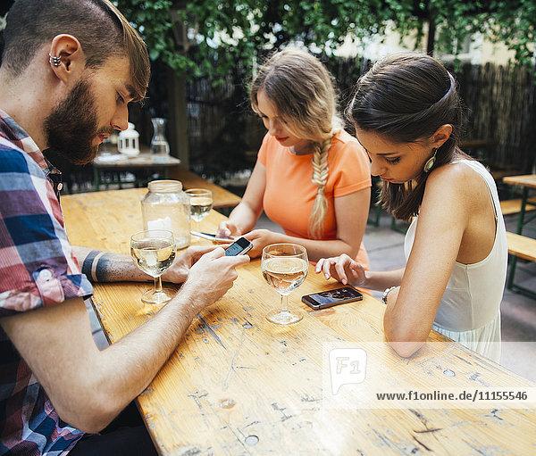 Freunde,  die Mobiltelefone benutzen und Schorle trinken in einem Pub im Freien