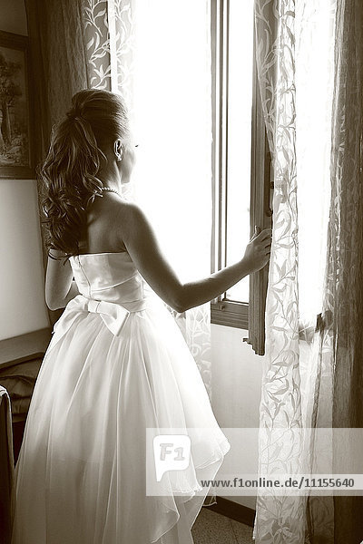 Caucasian bride looking out window