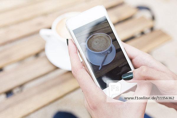 Frau fotografiert ihren Cappuccino mit Smartphone  Nahaufnahme