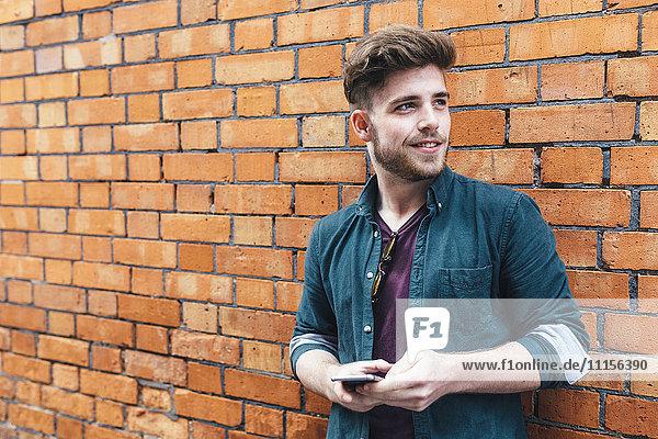 Portrait eines jungen Mannes mit Handy