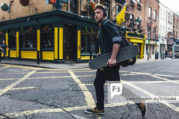 Irland  Dublin  junger Mann mit Kopfhörer und Skateboard über die Straße