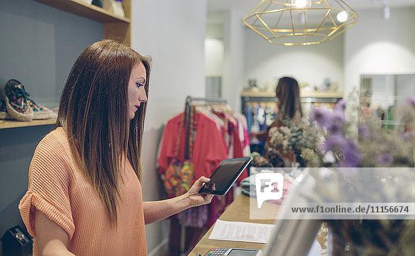 Verkäuferin mit Tablett am Tresen in einer Boutique