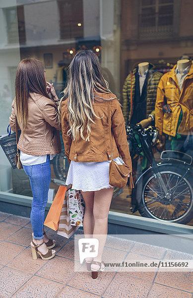 Zwei Frauen mit Einkaufstaschen am Schaufenster
