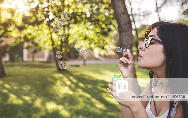 Junge Frau bläst Seifenblasen im Park