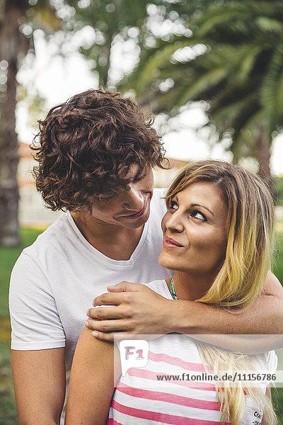 Lächelndes junges Paar umarmt im Park