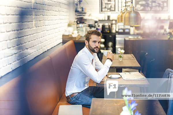 Geschäftsmann sitzend in einem Café mit Tasse Kaffee