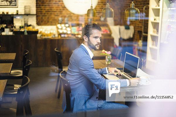 Geschäftsmann mit Laptop im Café