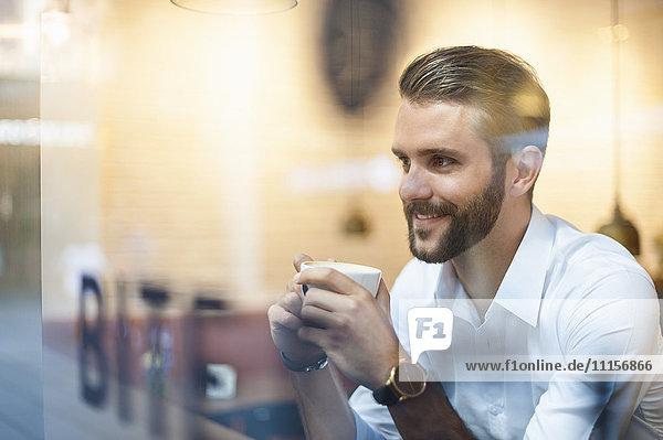 Lächelnder Geschäftsmann hält eine Tasse Kaffee hinter einer Fensterscheibe in einem Café.