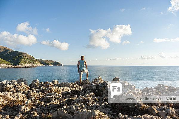 Spanien  Mallorca  Jogger auf Felsenküste stehend