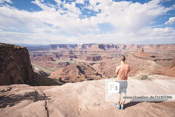 USA  Utah  Junger Mann am Dead Horse Point mit Blick auf den Colorado River