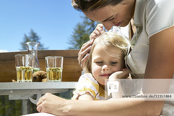 Mother and daughter relaxing on outdoor terrace
