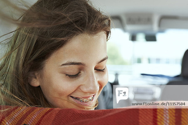 Smiling teenage girl with braces inside car