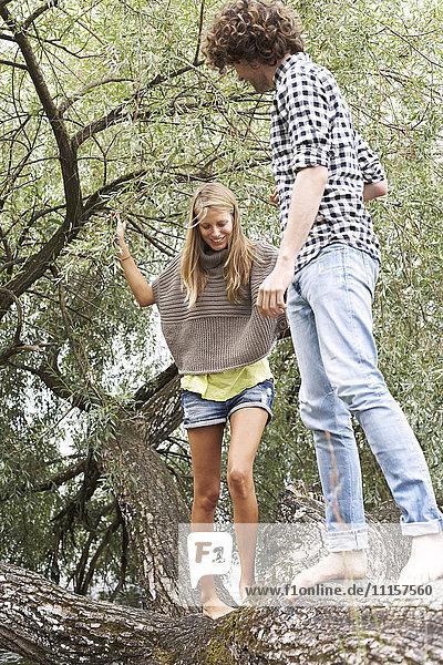 Junges Paar balanciert auf einem Baumstamm
