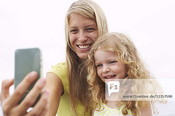 Lächelnde Mutter mit Tochter  die einen Selfie nimmt.