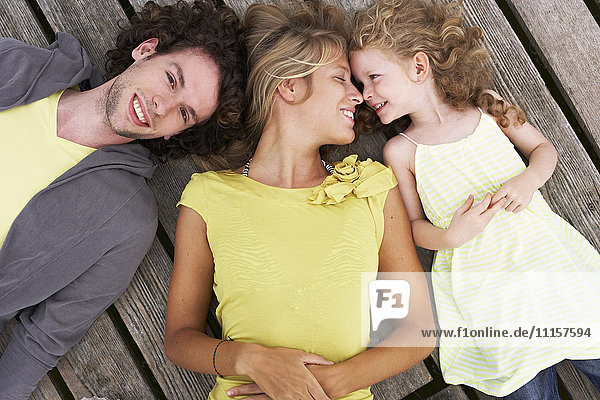 Smiling family lying on a jetty