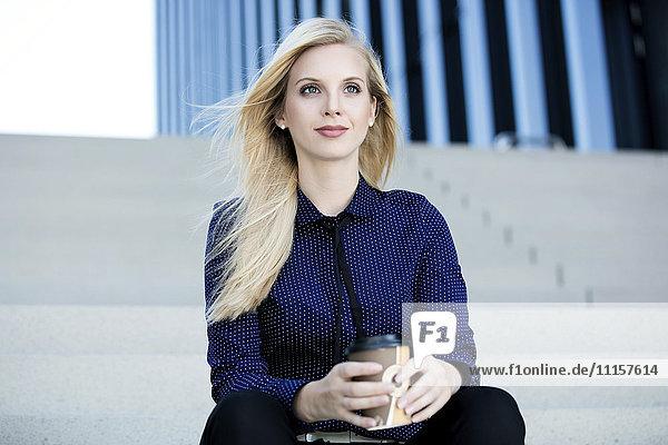 Porträt einer blonden Geschäftsfrau auf der Treppe mit Kaffee zum Mitnehmen
