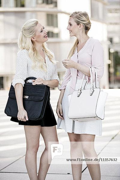 Zwei modische Geschäftsfrauen mit Taschen im Gespräch