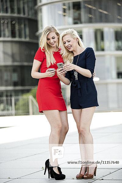 Zwei modische Frauen  die auf ihr Smartphone schauen