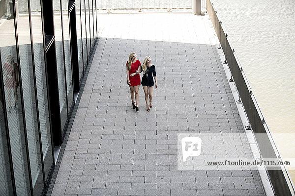 Zwei modische beste Freunde  die Arm in Arm auf einer Straße gehen.