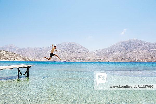Griechenland  Kykladen  Amorgos  Ägäis  nackter Mann  der von einem Holzsteg springt.