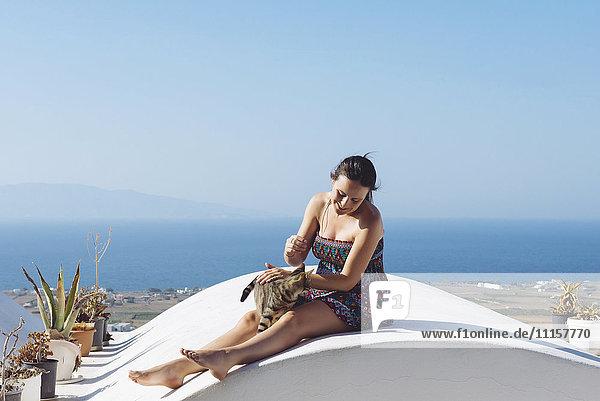 Griechenland  Santorini  Oia  Frau  die eine Katze streichelt
