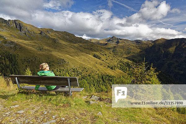 Österreich  Kärnten  Drautal  Frau auf Bank in der Berglandschaft