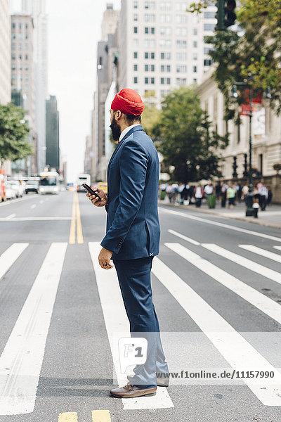 Indischer Geschäftsmann in Manhattan steht auf Zebrastreifen und hält ein Smartphone.