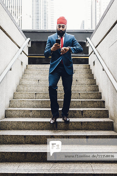 Indischer Geschäftsmann geht die Treppe hinunter  schaut auf die Uhr  hält das Smartphone.