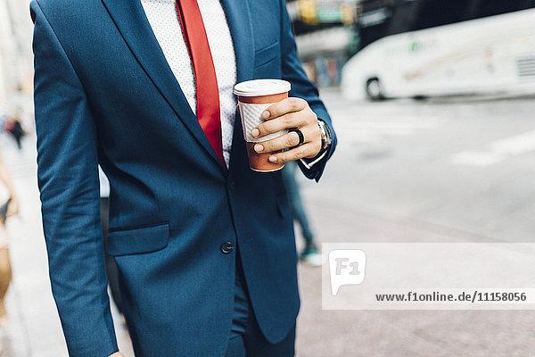 Geschäftsmann  der in der Stadt spazieren geht und eine Tasse Kaffee hält.