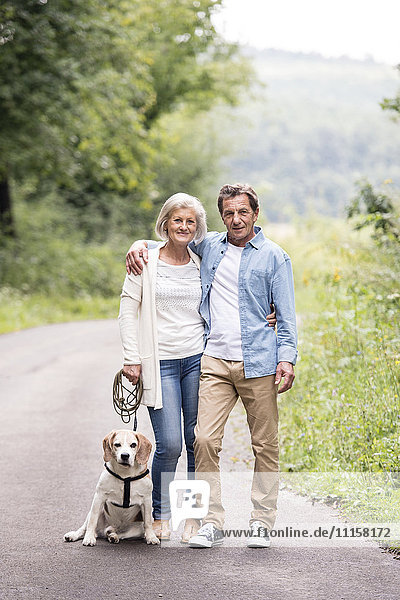 Portrait of happy senior couple with dog in nature