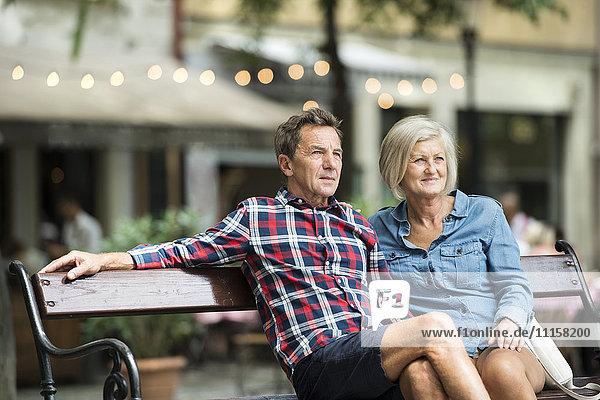 Seniorenpaar sitzt auf der Bank und schaut sich etwas an.