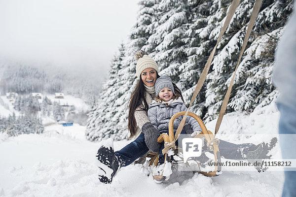 Glückliche Familie mit Schlitten in der Winterlandschaft
