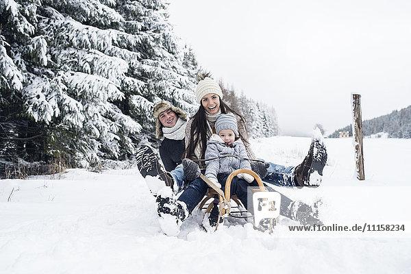 Glückliche Familie auf Schlitten in der Winterlandschaft