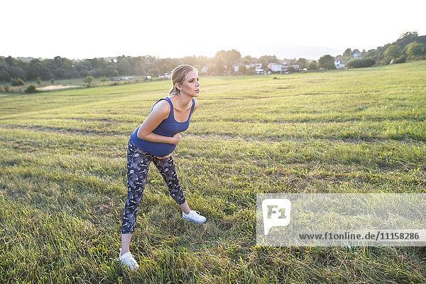 Schwangere Frau  die im Feld steht und Übungen macht.