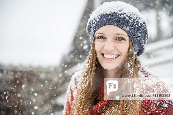 Portrait of smiling young woman in heavy snowfall
