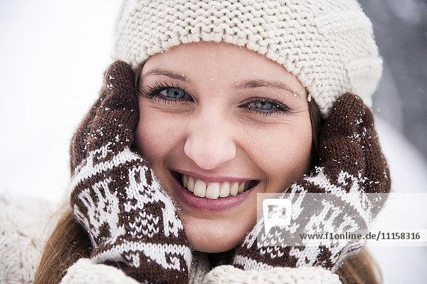 Porträt einer lächelnden jungen Frau im Schneefall