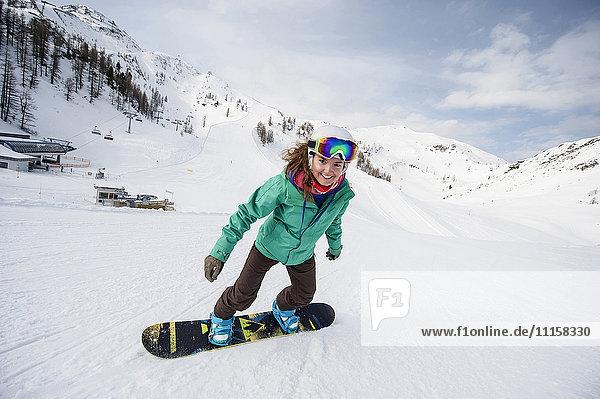 Österreich  Altenmarkt-Zauchensee  lächelnde junge Frau beim Snowboarden
