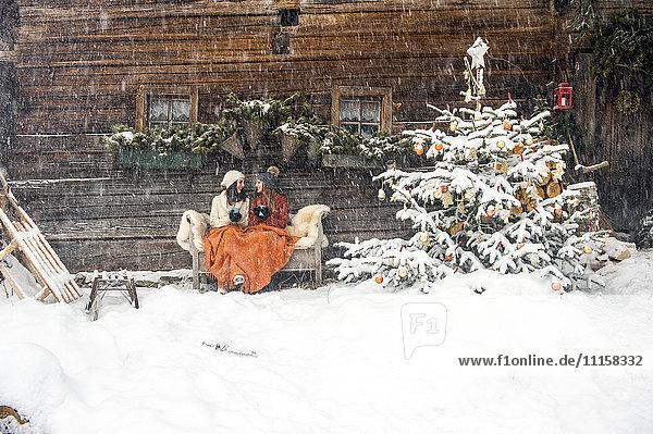 Freunde sitzen auf der Bank am Weihnachtsbaum vor der Berghütte