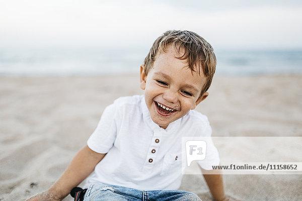 Ein lachender kleiner Junge spielt am Strand.