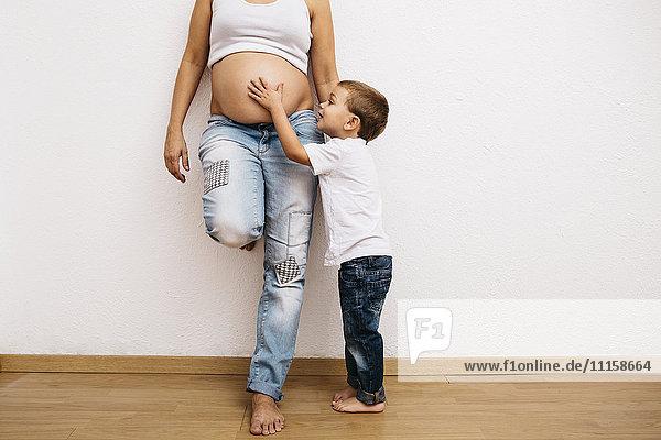 Kleiner Junge  der den Bauch einer schwangeren Mutter berührt.