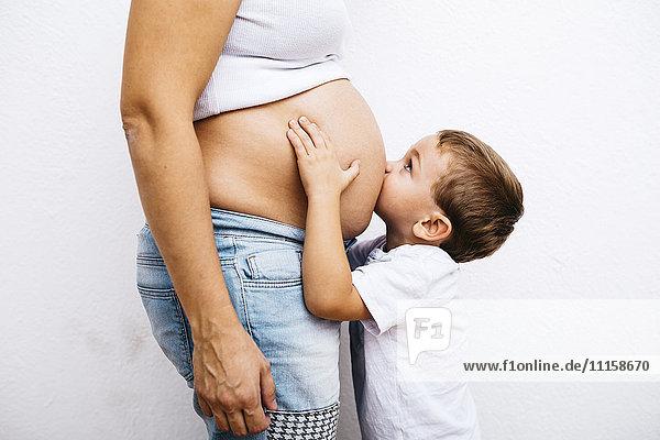 Kleiner Junge  der den Bauch einer schwangeren Mutter küsst.