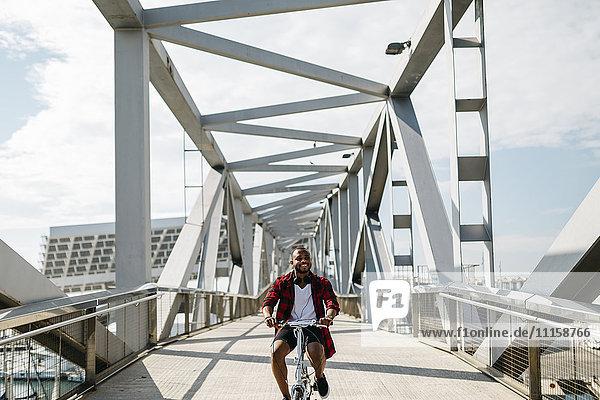 Lächelnder Mann beim Fahrradfahren auf einer Brücke