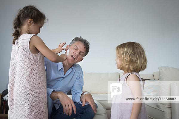 Tochter klebt Pflaster auf Vaters Wange