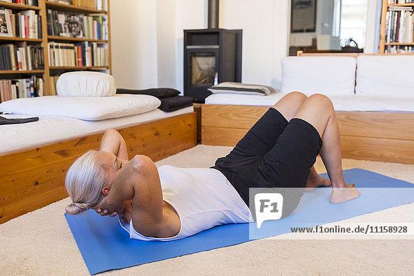 Frau trainiert auf Turnmatte im Wohnzimmer