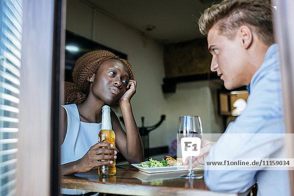 Junges Paar in einer Bar vom Fenster aus gesehen