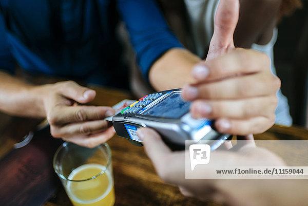 Nahaufnahme eines Mannes  der im Restaurant mit Kreditkarte bezahlt.