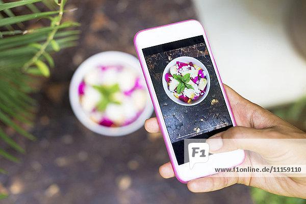 Frau fotografiert tropischen Obstsalat mit Handy  Nahaufnahme