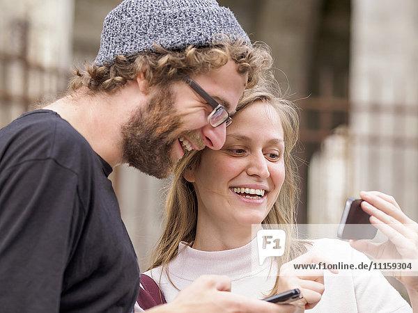 Lächelndes junges Paar beim Blick auf das Smartphone